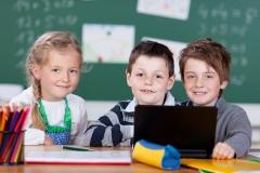 drei schulkinder arbeiten mit laptop